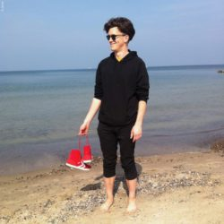Photo: Wille Felix Zante standing barefoot at the beach and holding his red shoes in his hands; Copyright: private