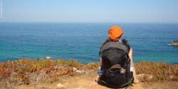 Photo: Theresa Steinkellner sitting with backpack in Portugal in front of the sea; Copyright: Theresa Steinkellner