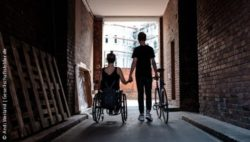 Foto: Young woman in a wheelchair holding hands with her boyfriend who walks next to her with his bike in the other hand; Copyright: Andi Weiland | Gesellschaftsbilder.de
