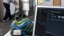 Photo: Shoe with sensor on it placed beside a notebook whille a gait analysis of a Parkinson patient is taking place in the background; Copyright: Kurt Fuchs