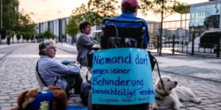 "Photo: The back of a wheelchair with a poster saying: ""Nobody may be disadvantaged because of his disability""; Copyright: Andi Weiland 