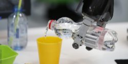 Photo: Robot gripping arm pours in some water in a cup; Copyright: Messe Düsseldorf/ctillmann