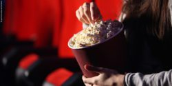 Photo: Young woman eating popcorn in the cinema