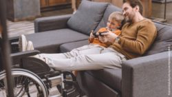 Photo: A young father sits on the sofa with his son and plays a video game. He has put his feet on his wheelchair.; Copyright: panthermedia.net/ArturVerkhovetskiy