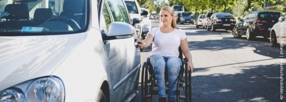 Photo: Young woman in a wheelchair opens the driver's door of the car she wants to get into; Copyright: visitBerlin, Andi Weiland | Gesellschaftsbilder.de