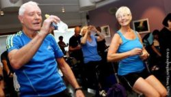 Photo: Elderly man and woman during a spinning class. He is drinking water, she is smiling at him; Copyright: Andrea Hegdahl Tiltnes, NTNU