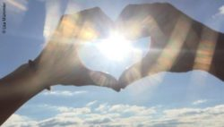 Photo: Lizzi's hands form a heart and are stretched out into the sky. Through the heart you can see the sun; Copyright: Lisa Mümmler