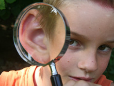 Photo: Boy with magnifying glass over the ear