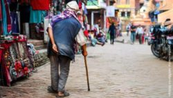 Photo: Elderly man with walking aid standing on an exotic market; Copyright: panthermedia.net/Martin Molcan