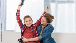 Photo: Mother embracing her celebrating son who completed a video game; Copyright: panthermedia.net/IgorVetushko