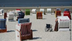 Photo: A lot of beach chairs, in between a wheelchair in the sand; Copyright: panthermedia.net/Antje Lindert-Rottke