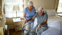 Photo: An older couple, where she helps her husband out of bed.; Copyright: panthermedia.net/daviles