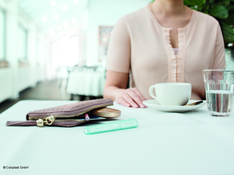 Photo: Woman in a café, the catheter lying next to her bag