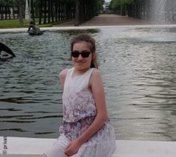 Photo: Laura Mench sits at the edge of a fountain and smiles into the camera; Copyright: private