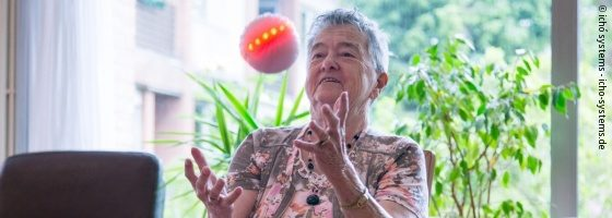 Photo: An elderly lady catching ichó. The ball starts to glow in red and orange colors.; Copyright: ichó system - icho-system.de