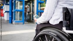 Photo: Wheelchair user stands in front of an elevator and holds a mobile phone in her hand, on which an app displays  elevator problems; Copyright: Andi Weiland | Gesellschaftsbilder.de