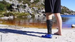 Photo: Man standing at a lake. He wears the Mecuris NexStep prosthetic foot and a cover; Copyright: Mecuris