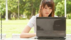 Photo: Young woman is concentrated while using a laptop; Copyright: panthermedia.net/achaphoto