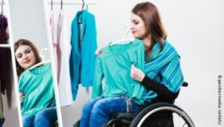 Photo: Young woman in a wheelchair trying on clothes in front of a mirror; Copyright: panthermedia.net/akz