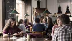 Photo: Several talking young people in a café; Copyright: Oticon