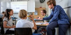 Photo: Four pupils sitting at a desk in their classroom. One of them is using a wheelchair; Copyright: Andi Weiland | Gesellschaftsbilder.de