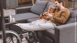 Photo: A young father sitting on the sofa playing a video game with his son. He has put his feet on his wheelchair; Copyright: panthermedia.net/ArturVerkhovetskiy