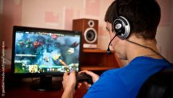 Photo: Gamer with a headset in front of his home screen; Copyright: panthermedia.net/IrynaTiumentsev