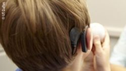 Photo: A boy from the back, so his cochlear implant is visible; Copyright: UT Dallas