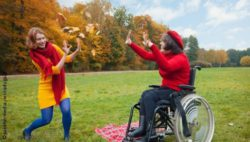 Photo: Two women - one in a wheelchair - throw autumn leaves at each other; Copyright: panthermedia.net/raduga21