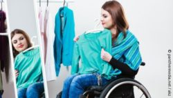 Photo: Woman in a wheelchair trying on a shirt; Copyright: panthermedia.net/akz