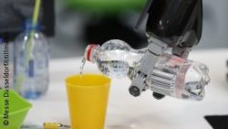 Photo: Robot gripping arm pours in some water into a cup; Copyright: Messe Düsseldorf/ctillmann