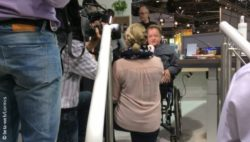 Photo: Interview with wheelchair user in front of a camera; Copyright: beta-web/Lormis