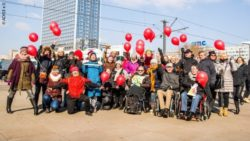 Photo: A group of people with red balloons at an event for Rare Disease Day in Berlin; Copyright: ACHSE e.V.