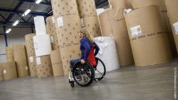 Photo: Wheelchair user driving through a warehouse; Copyright: O4 Wheelchairs GmbH