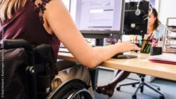 Photo: A wheelchair user sits at her desk in the office and works on the computer; Copyright: Andi Weiland | Boehringer Ingelheim, Gesellschaftsbilder.de