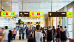 Photo: Airport terminal with people hurrying to the gates and directin signs above them ; Copyright: PantherMedia/anclave