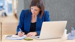 Photo: Business woman sitting at a laptop and taking handwritten notes; Copyright: PantherMedia/mavoimages