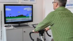 Photo: Older man on a home trainer while he is playing an exergame on the monitor in front of him; Copyright: TU Darmstadt, FG Multimedia Kommunikation