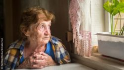 Photo: Elderly woman sitting alone in her house and looking out of the window; Copyright: PantherMedia/dimaberkut