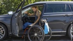 Photo: Man gets out of his converted vehicle into his wheelchair; Copyright: BG BAU/Rolf Schulten