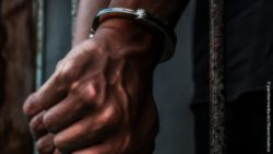 Photo: Hands of a male person of color with handcuffs; Copyright: panthermedia.net/thawornnulove