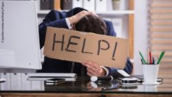 "Photo: Employee at his desk holding a ""Help""-sign in front of the camera; Copyright: panthermedia.net/Andriy Popov"