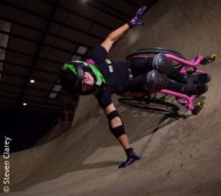 Photo: a young woman – Lily Rice – is wearing a helmet and doing a stunt in a pink wheelchair; Copyright: Steven Clarey