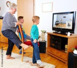 Photo: Elderly lady practicing an exergame together with her grandchildren; Copyright: Universität Siegen