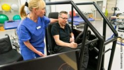 Photo: A female therapist in blue hospital working clothes in standing next to a man. He is sitting in a training device with a seat and a steering wheel; Copyright: Automobile Sodermanns