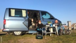 Photo: Michel Arriens and Franziska Stoldt sitting in front of their VW Bulli bus on a camping site; Copyright: private