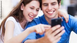 Image: A young woman and a young man are using a smartphone together; Copyright: PantherMedia/pikselstock
