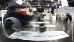 Photo: wheelchair user in a blurred photo effect drives over a people with disabilities and jobs sign at REHACARE trade fair; Copyright: Messe Düsseldorf/ctillmann