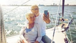 Photo: Elderly man and elderly woman make a selfie of themselves smiling while they are on a sailboat; Copyright: panthermedia.net/Lev Dolgachov