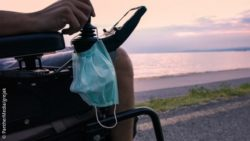 Photo: Close-up of a man in an electric wheelchair, a mouth and nose protector is attached to the control unit. In the background you can see the sea at sunset; Copyright: PantherMedia/grejak